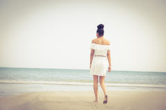 Stylish woman walking on the sand Stock Images