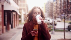Woman walking on street. Drink coffee and using smartphone. stock video footage