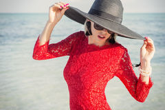 Stylish woman wearing black summer hat and red dress on beach Royalty Free Stock Photography