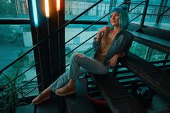 Stylish woman wearing a blue wig sitting on stairs in a modern. Stylish woman wearing a blue wig, jeans and a golden blouse sitting, laying on stairs while stock image