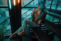 Stylish woman wearing a blue wig sitting on stairs in a modern. Stylish woman wearing a blue wig, jeans and a golden blouse sitting on stairs while thinking in a stock image