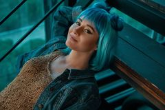 Stylish woman wearing a blue wig sitting on stairs in a modern. Beautiful woman wearing a blue wig, jeans and a golden blouse laying on stairs while relaxing in stock images