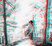 Anaglyph effect of woman in the forest. Stylish woman wearing in a hat and poncho standing in the forest among trees, rear view. Image with anaglyph effect stock images