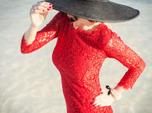 Stylish woman wearing red dress and black hat Stock Photography