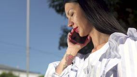 Stylish woman in white blouse answering the call on her phone. Stylish woman in white stripped blouse is sitting on a bench in park and talking on phone. Blue stock video