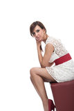 Stylish woman in a white miniskirt. Stylish woman in an elegant white miniskirt and high heels sitting on a small square leather seat in profile looking at the Royalty Free Stock Photos