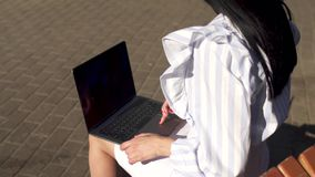 Brunete typing on laptop sitting on a bench in park. Stylish woman in white stripped blouse is sitting on a bench in park and typing on her laptop. Fashionable stock video