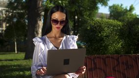 Stylish brunette in sunglasses typing on laptop sitting on a bench in park. Stylish woman in white stripped blouse is sitting on a bench in park and typing on stock footage