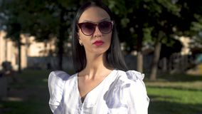 Beautiful young woman in sunglasses typing on her laptop in park. Stylish woman in white stripped blouse is sitting on a bench in park and typing on her laptop stock video