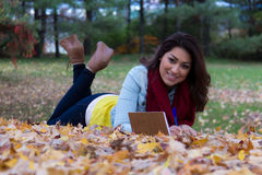 Stylish woman writing in her notebook outdoors during autumn Stock Photo