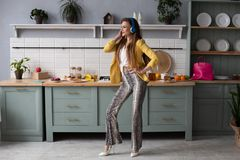 Stylish woman in yellow jacket and blue headphones singing. stock photography