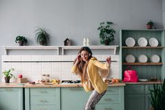 Stylish woman in yellow jacket and blue headphones singing. stock photos