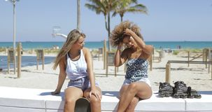Stylish women chilling on coastline in sunshine. Confident diverse women sitting on tropical coastline in sunshine and talking in leisure relaxing together stock video footage