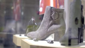 Stylish women`s boots. Stylish black leather women`s boots on the shelf in the shop. Pavilion of the store with fashionable female shoes. Leather autumn and stock video footage