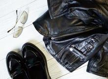 Stylish women's clothing. Ladies black leather jacket, fashion Lofer and glasses on a white wooden background Royalty Free Stock Image