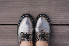 Stylish women`s leather shoes with laces on a wooden board, contrasting objects royalty free stock photo