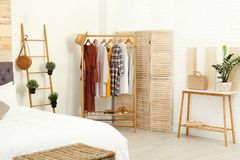 Stylish wooden table and rack with clothes in modern bedroom royalty free stock photos