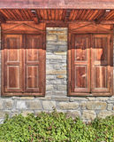 Stylish wooden windows on stone wall Royalty Free Stock Images
