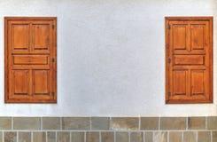 Stylish wooden windows on stone wall Royalty Free Stock Photo