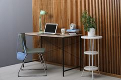 Stylish workplace interior with laptop on table near wooden wall royalty free stock image