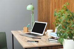 Stylish workplace interior with laptop on table near wooden wall royalty free stock photo