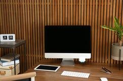 Stylish workplace with modern computer near wall. Space for text. Stylish workplace with modern computer near wooden wall. Space for text stock photos