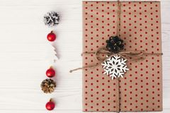 Stylish wrapped gift box top view, with golden ornaments and con. E. craft present flat lay. seasonal greetings, happy holidays. merry christmas and happy new Stock Photo