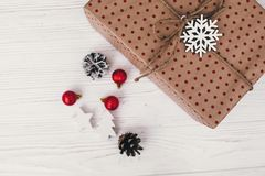 Stylish wrapped gift box top view, with golden ornaments and con. E. craft present flat lay. seasonal greetings, happy holidays. merry christmas and happy new Royalty Free Stock Photo