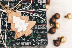 Stylish wrapped gift box top view, with golden ornaments and tre. E. modern present. seasonal greetings, happy holidays. merry christmas and happy new year Stock Photo