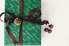 Stylish wrapped gift box top view, with ornaments and cone. gree. N present flat lay. seasonal greetings, happy holidays. merry christmas and happy new year Royalty Free Stock Image
