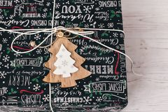 Stylish wrapped gift box top view, with wooden ornament tree. mo. Dern present on rustic wood. seasonal greetings, happy holidays. merry christmas and happy new Royalty Free Stock Image