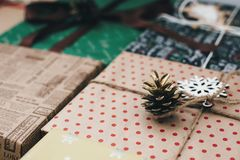 Stylish wrapped gift boxes, with ornaments tree pine cones and t. Wine. space for text. craft paper. merry christmas and happy new year concept. seasonal Royalty Free Stock Photography