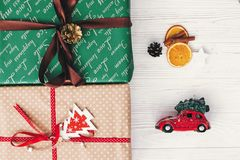 Stylish wrapped gift boxes top view, with ornaments tree pine co. Nes and car toy with tree and orange. merry christmas and happy new year concept. flat lay Stock Photography