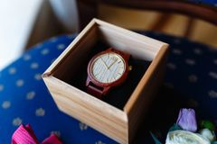 Stylish wristwatch in a wooden box. In background Pink bow tie, beautiful glass cufflinks, flower boutonniere. A men's set of acc. Essories on an old wooden Royalty Free Stock Photography