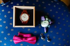 Stylish wristwatch in a wooden box. Pink bow tie, beautiful glass cufflinks, flower boutonniere. A men's set of accessories on an. Old wooden chair with a soft Stock Photo
