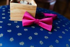 Stylish wristwatch in a wooden box. Pink bow tie. A men's set of accessories on an old wooden chair with a soft blue seat. Set of. Accessories for a business Stock Image