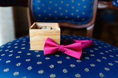 Stylish wristwatch in a wooden box. Pink bow tie. A men's set of accessories on an old wooden chair with a soft blue seat. Concep. T of business accessories in Stock Photography