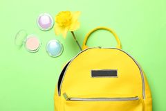 Stylish yellow backpack with narcissus and cosmetics for eyes royalty free stock photography