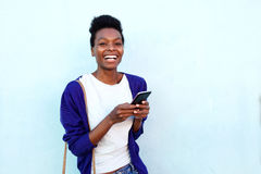 Stylish young african female with mobile phone. Portrait of stylish young african female standing against blue background with mobile phone Royalty Free Stock Image