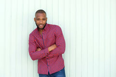 Stylish young african man with arms crossed standing by wall Stock Image