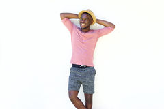 Stylish young african man standing relaxed. Portrait of young african man standing with his hands behind head against white background Royalty Free Stock Photography