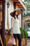 Stylish young asian girl standing on city street against cafe facade royalty free stock photo