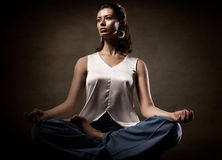 Stylish young athletic girl in fashionable clothes, showing yoga asanas in the studio. Beauty face and body health. Stock Photos
