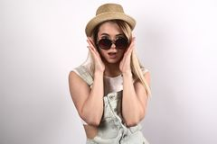 stylish young attractive woman does not believe his eyes. A surprised shocked expression dreamy. Sunglasses and hat, hands are royalty free stock photo
