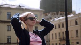 Stylish young beautiful blonde girl on a sunny day posing at sunny city street stock video footage