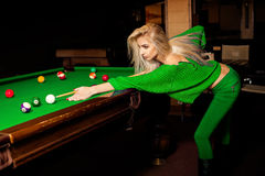 Stylish young beautiful blonde plays pool billiard Stock Image