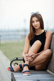 Stylish young beautiful hipster woman sitting on the park bench Royalty Free Stock Image