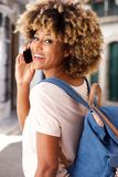 Stylish young black woman standing outdoors and making phone call. Close up portrait of stylish young black woman standing outdoors and making phone call Royalty Free Stock Photo
