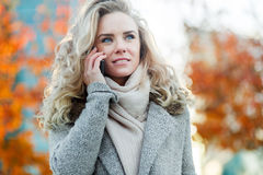 Stylish young blond woman speaking on phone outdoors Royalty Free Stock Image