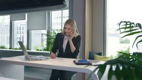 Trendy business woman watching laptop and speaking on phone. Stylish young blond woman working in office at table. Stylish young blond woman working in office at stock video footage